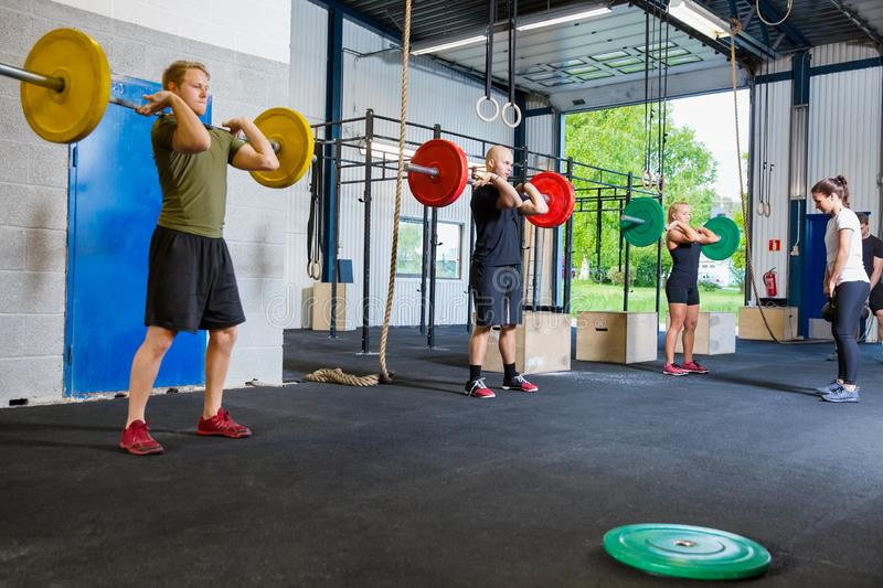 Team training with weights and kettlebells at fitness gym royalty free stock photos