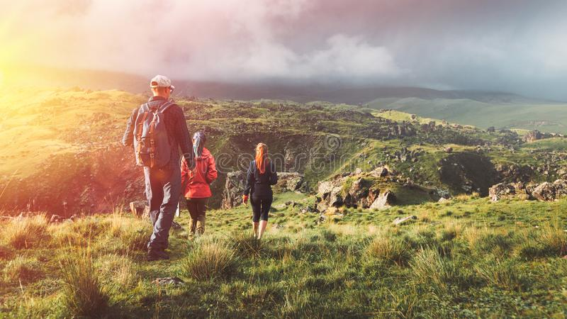 Group Of Hikers Walking Along The Green Hills, Rear View. Travel. Group Of Travelers Walking Along The Green Hills, Rear View. Travel Tourism Discovery Concept royalty free stock photo