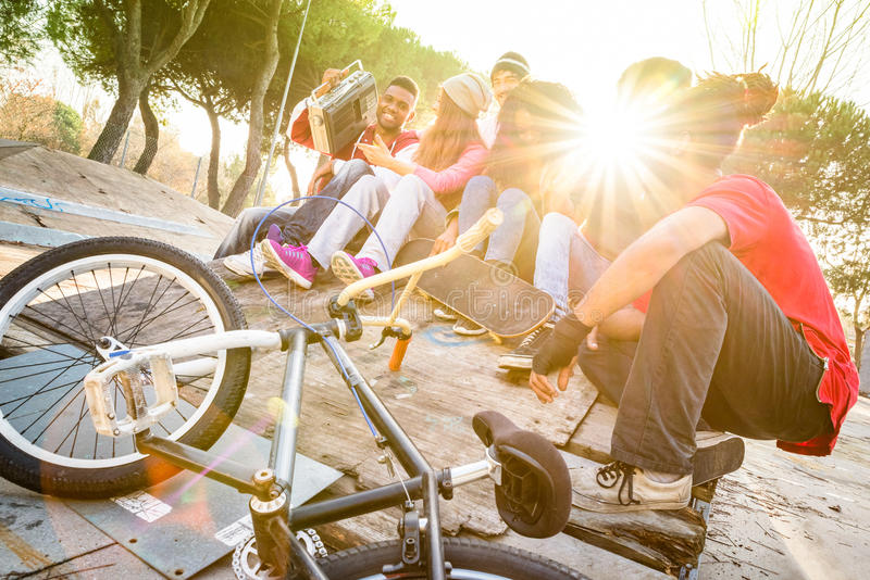 Group of trendy friends having fun together at skate bmx park stock images