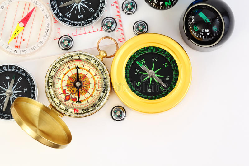 Group of twelve small and big compasses. Group of twelve different small and big compasses on white background stock photos
