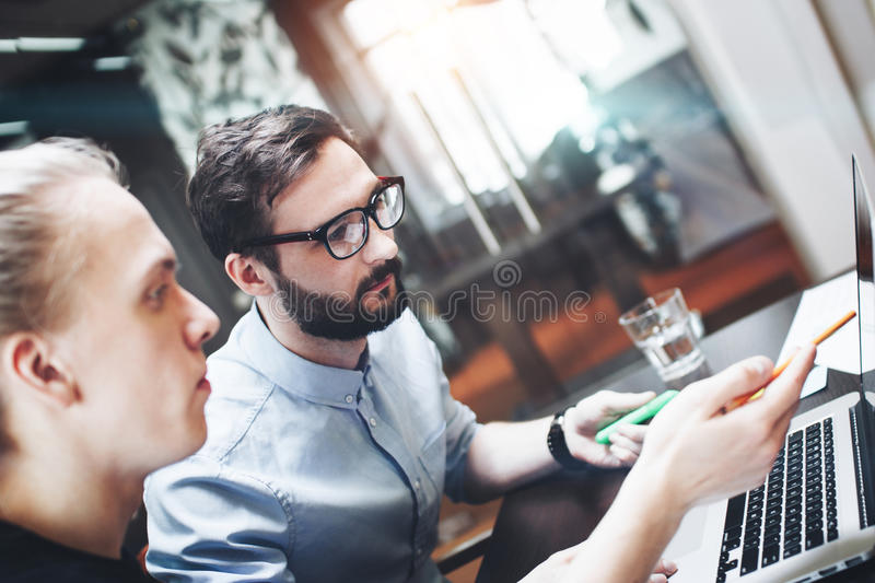 Group of two coworkers making brainstorming a new ideas in modern loft office. Teamwork at laptop, work with papers, training pl stock photography