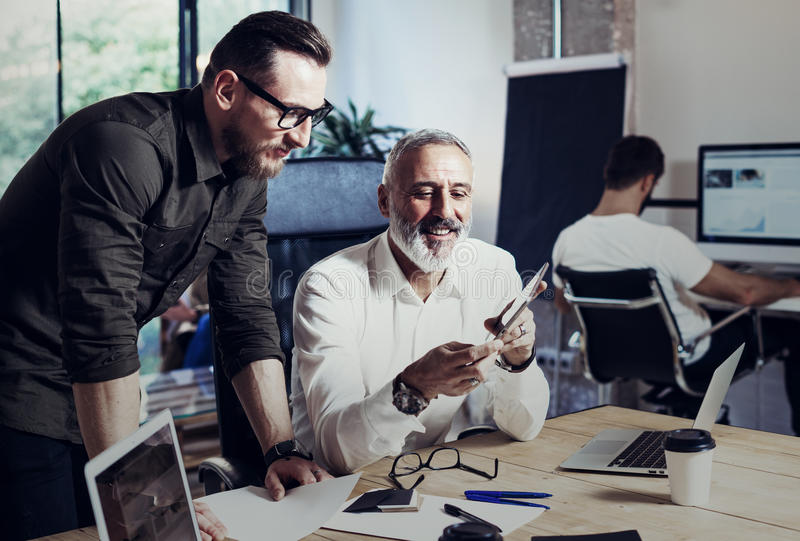 Group of two coworkers making great time brake during working process in modern office.Adult bearded man watching video royalty free stock photography