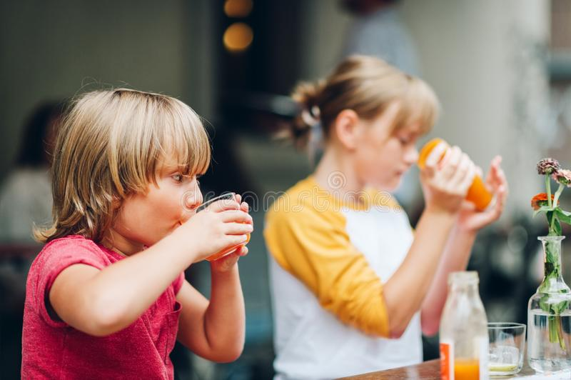 Group of two funny kids having drink in cafe royalty free stock images