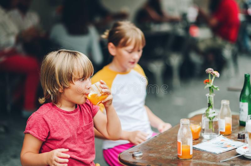 Group of two funny kids having drink in cafe stock images