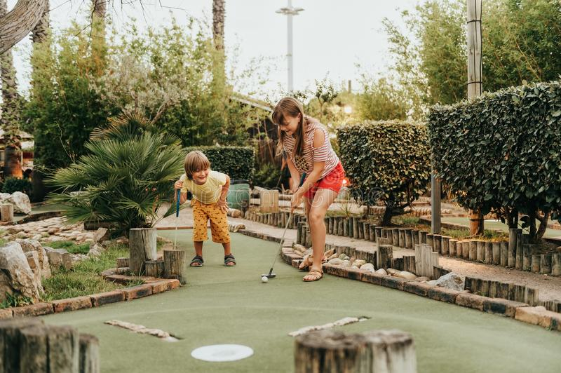 Group of two funny kids playing mini golf stock image