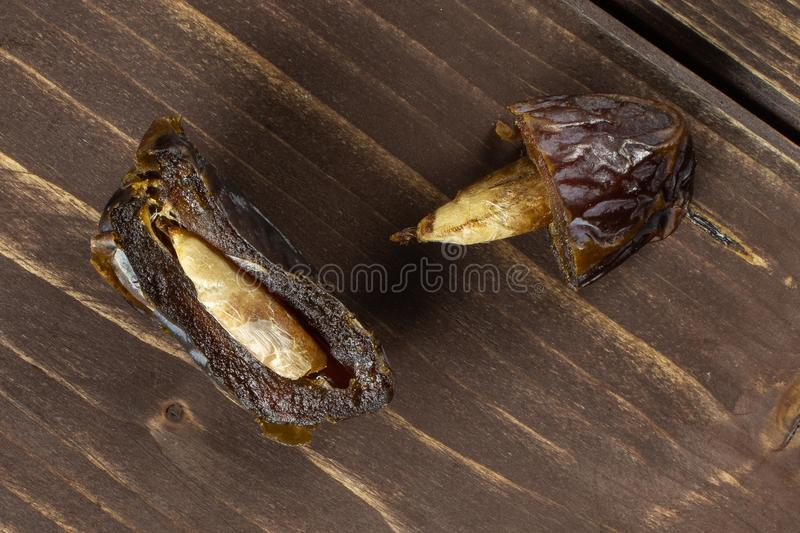 Dried date medjool on brown wood. Group of two halves of dried brown date medjool flatlay on brown wood royalty free stock image