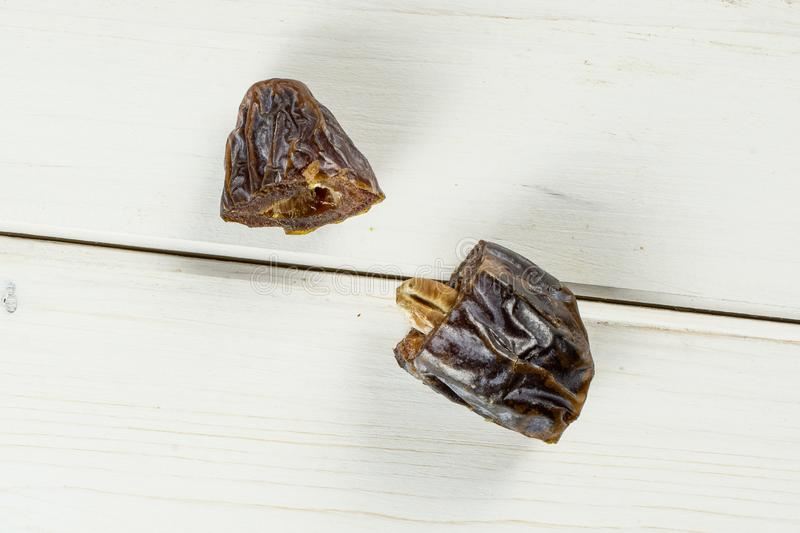 Dried date medjool on grey wood. Group of two halves of dried brown date medjool flatlay on white wood stock photo