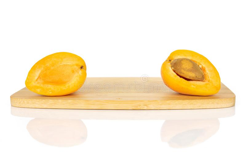 Fresh orange apricot isolated on white. Group of two halves of fresh orange apricot with an apricot stone on a bamboo cutting board isolated on white background stock photo