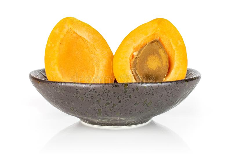 Fresh orange apricot isolated on white. Group of two halves of fresh orange apricot with an apricot stone in a dark ceramic bowl isolated on white background stock photos