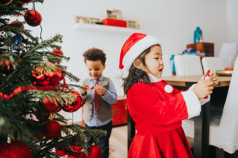 Two adorable 3 year old kids playing by the Christmas tree stock images