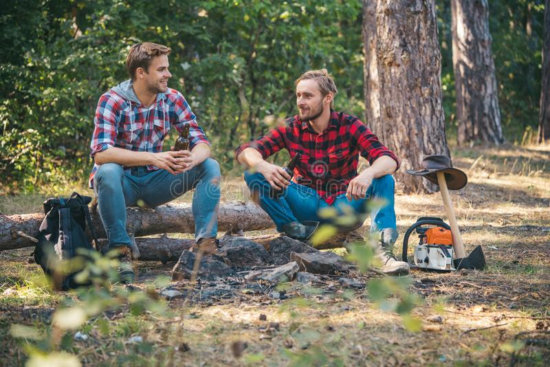 Group of two male backpackers relaxing near campfire. Young man having picnic in woods. Friends sit on forest picnic stock photo