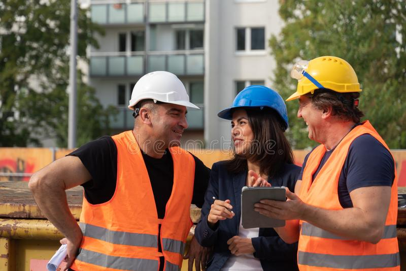 Group of male and female workers on construction site stock photos