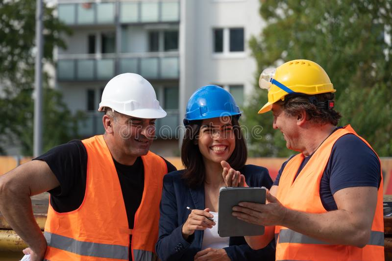Group of male and female workers on construction site stock photography