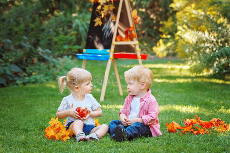 Group of two white Caucasian toddler children kids boy and girl sitting outside in summer autumn park by drawing easel. Looking at each other, playing eating royalty free stock photos