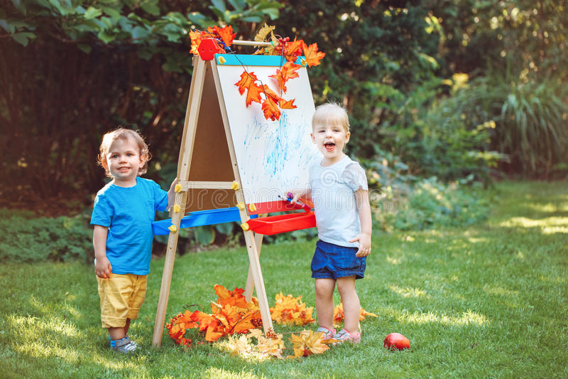 Group of two white Caucasian toddler children kids boy and girl standing outside in summer autumn park by drawing easel royalty free stock images