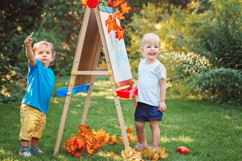 Group of two white Caucasian toddler children kids boy and girl standing outside in summer autumn park by drawing easel. With markers, playing studying learning royalty free stock photos