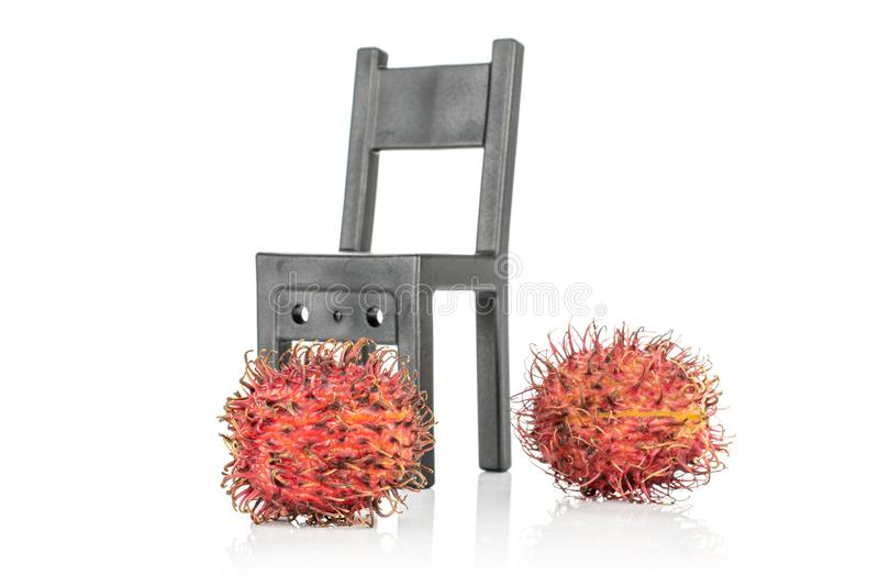 Fresh red rambutan isolated on white. Group of two whole fresh red rambutan with black chair isolated on white background royalty free stock images