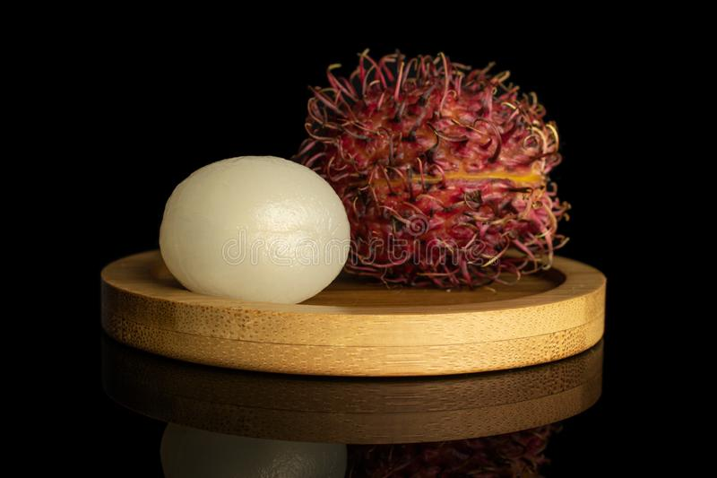 Fresh red rambutan isolated on black glass. Group of two whole fresh red rambutan one peeled on bamboo plate isolated on black glass royalty free stock images