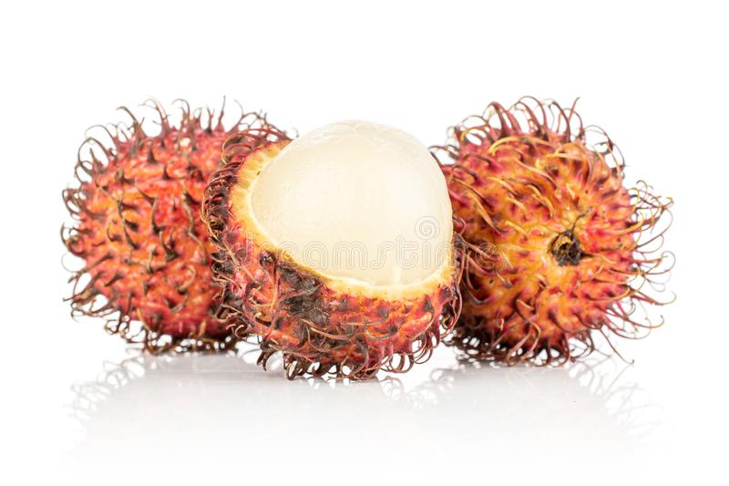 Fresh red rambutan isolated on white. Group of two whole one half of fresh red rambutan isolated on white background royalty free stock photography