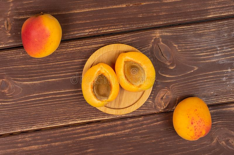 Fresh orange apricot on brown wood. Group of two whole two halves of fresh orange apricot with an apricot stone on a round bamboo coaster flatlay on brown wood stock image
