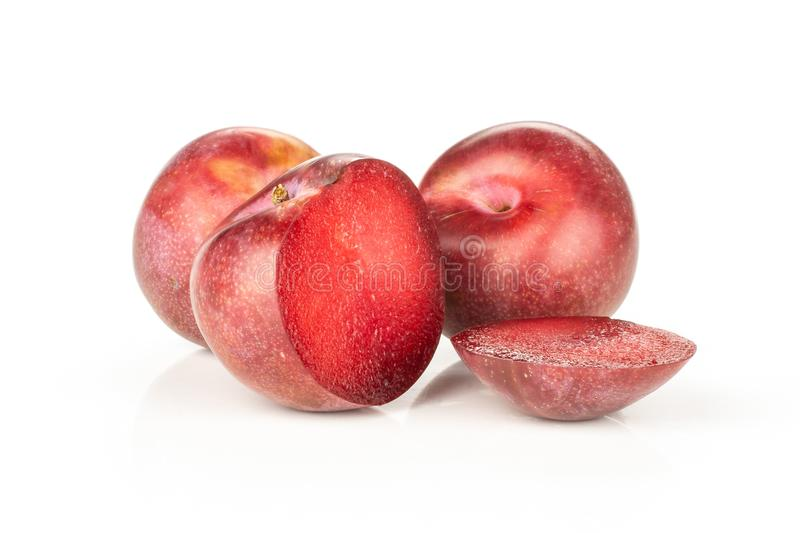 Fresh pluot interspecific plums isolated on white. Group of two whole two halves of fresh pluot interspecific plums variety one sliced isolated on white stock photo