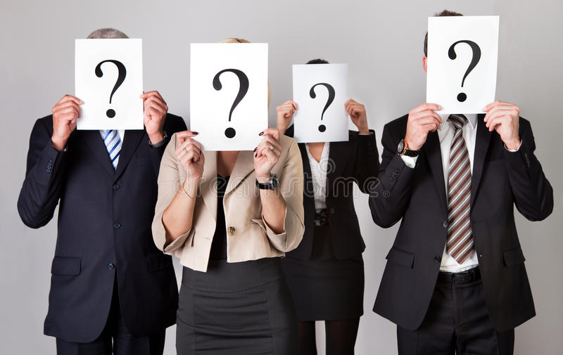 Group of unidentifiable business people. Hiding under question marks stock photography
