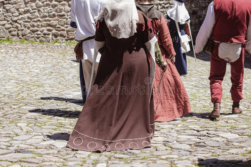 Group of unrecognizable people dressed in medieval costumes walking stock images