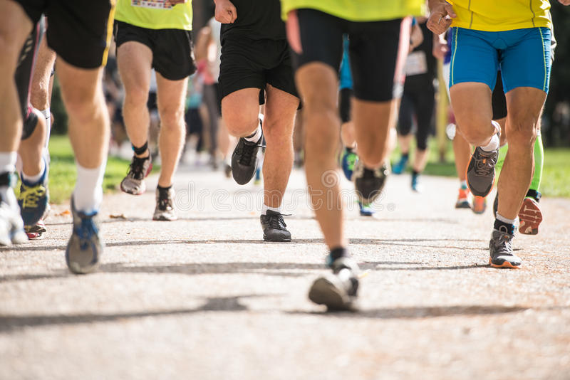 Group of unrecognizable runners outdoors. Long distance running. Group of unrecognizable runners sprinting outdoors. Sportive people training in a urban area stock images