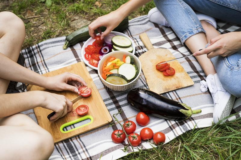 Unrecognizable teenagers camping and cooking. stock image