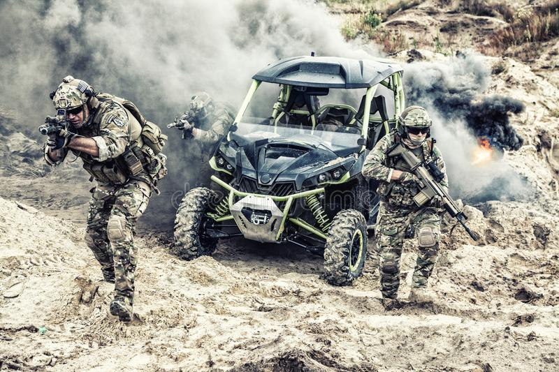 Patrol of three soldiers on buggy attacking enemy royalty free stock photos