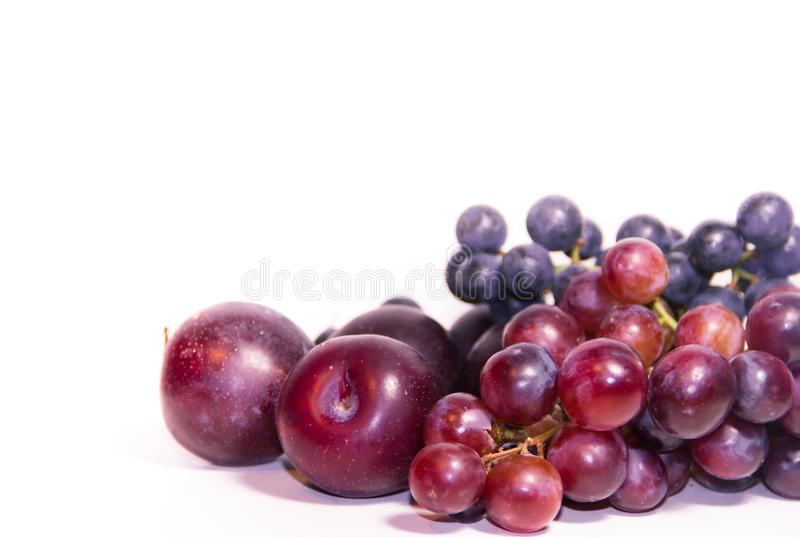Group of varied grapes and plums in ultra violet colors. Variety of grapes and plums in ultra violet colors stock image