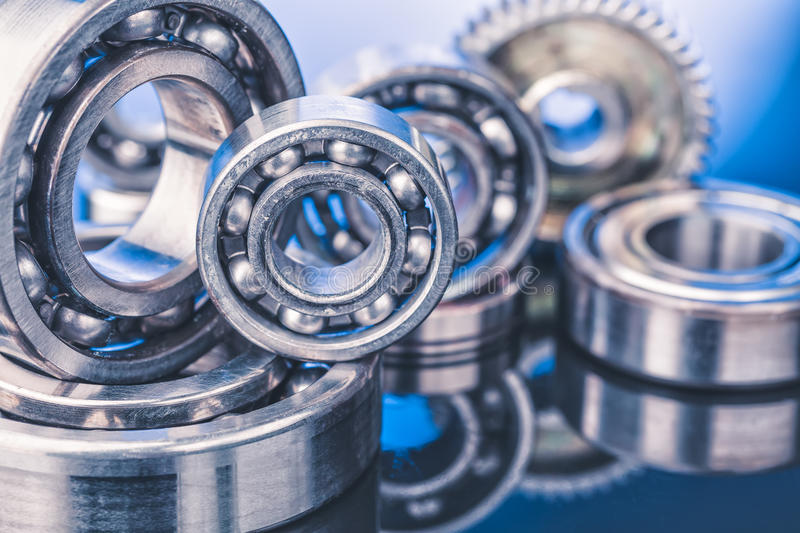 Group of various ball bearings close up on nice blue background with reflections.  royalty free stock photography