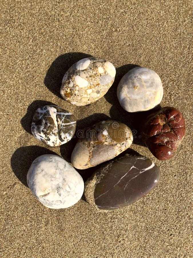 Group of various sea stones on sand. View from above, background. stock image