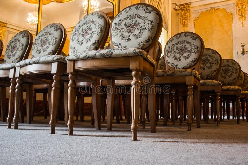 A group of vintage wooden chairs stands in several rows in a large old room with a luxurious interior. empty auditorium in the. Assembly hall. hall for stock photos