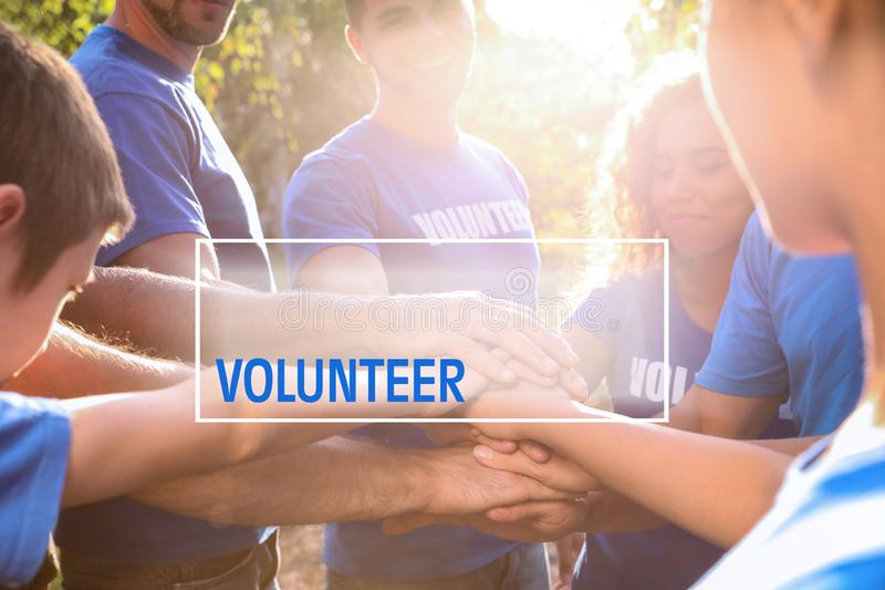Group of volunteers joining hands together outdoors stock photo
