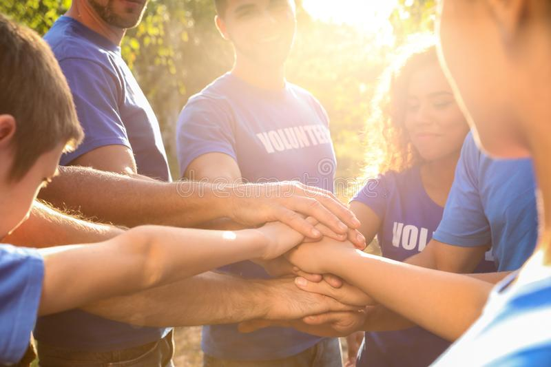 Group of volunteers joining hands together on sunny day stock photography