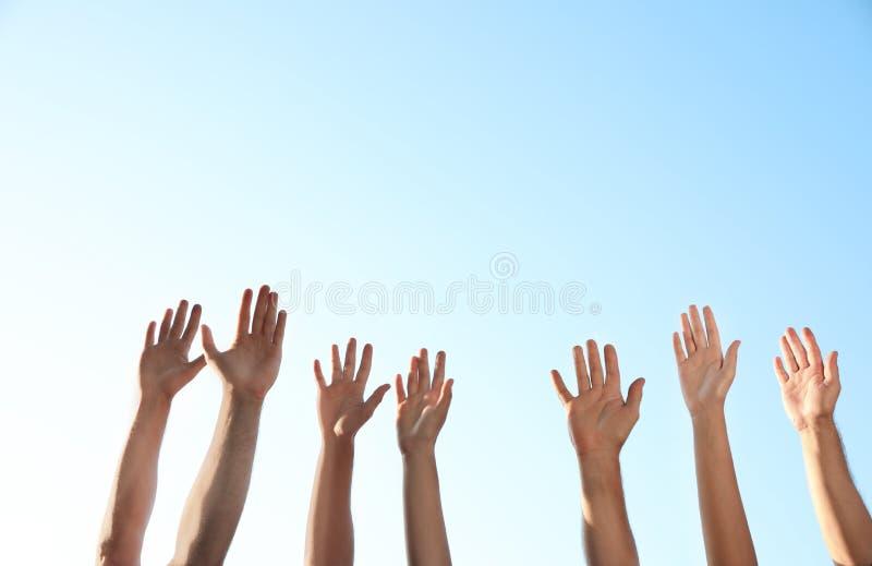 Group of volunteers raising hands outdoors. Closeup royalty free stock photo