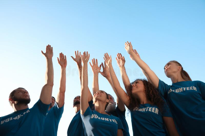 Group of volunteers raising hands outdoors stock images