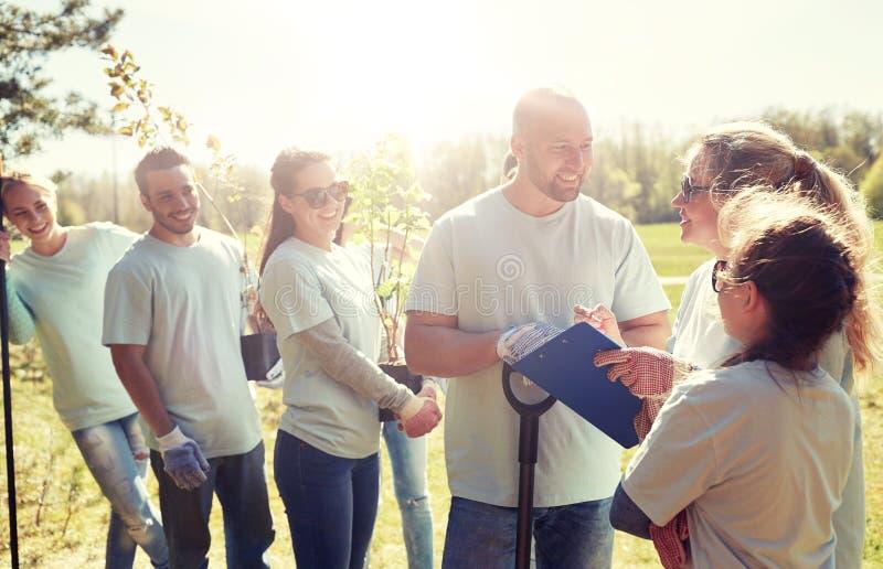 Group of volunteers with tree seedlings in park stock image