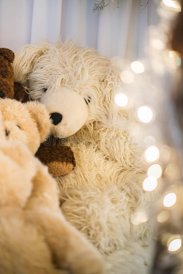 Group teddy bears lay indoor next to each other under the warm christmas lights royalty free stock photos