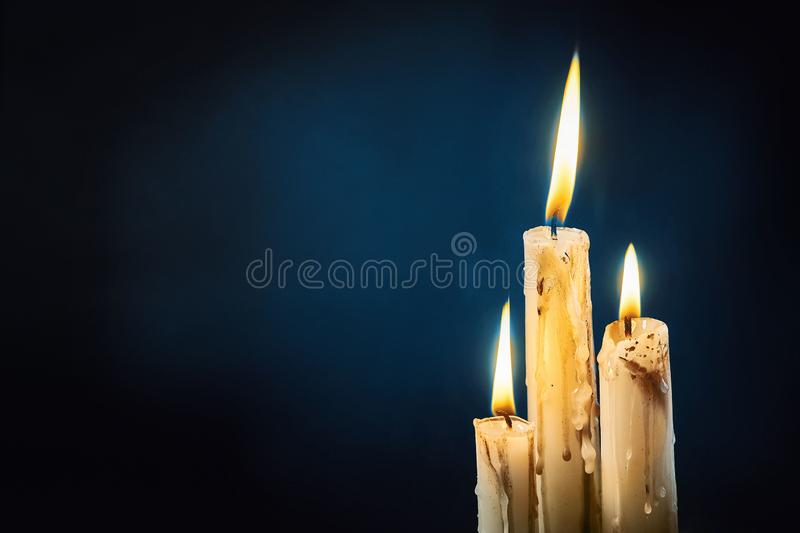 Group of white candles burning in the dark stock photography