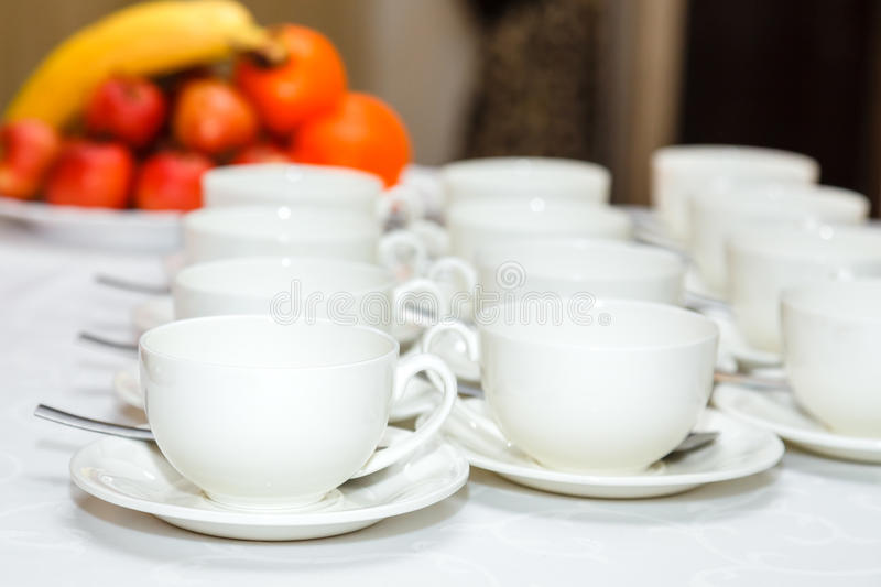 Group of white coffee cups and fruits stock photo
