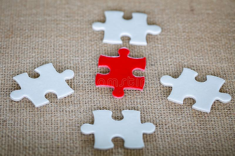 A group of white and red jigsaw puzzles placed on hemp sacks stock photo