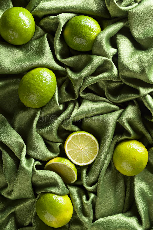 Group of whole and cut fresh limes on green satin stock photos