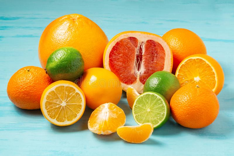 Group of whole and sliced citrus fruits - tangerines, lemons, limes, oranges, grapefruits on the surface of the blue stock images