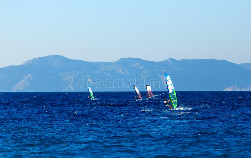 Group of windsurfers on a background mountains in the Aegean sea . Greece. Group of windsurfers on a background of mountains in the Aegean sea royalty free stock photo