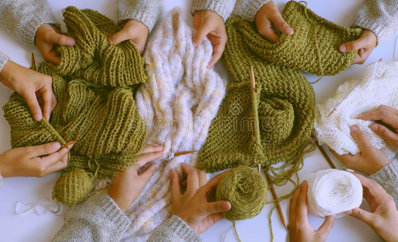 Group of woman hand with knitting needles, knit wool white and mossy green scarf for winter handmade gift. Amazing scene from indoor top view, group of woman stock photo