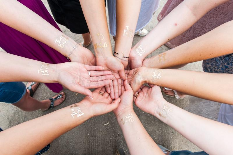 Group of woman holding hands with golden tattoo royalty free stock image