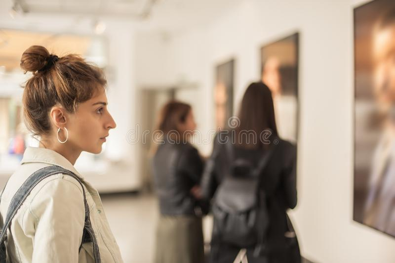 Group of woman looking at modern painting in art gallery royalty free stock images