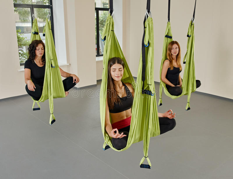 Group women anti-gravity aerial yoga portrait. Young women posing in anti-gravity aerial yoga green hammock. indoor fitness club. break relax. shot from above royalty free stock photo